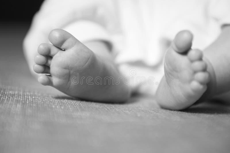 Petite pose infantile de sommeil de bébé garçon, pieds, au foyer neut photo libre de droits