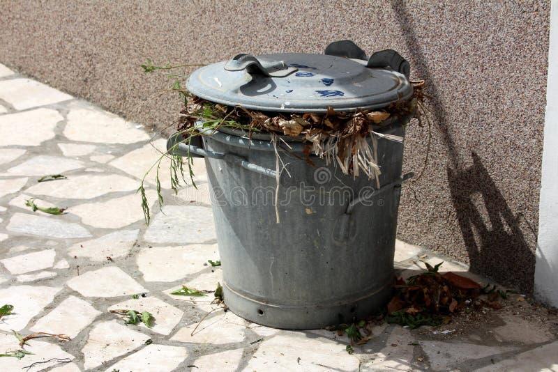 Petite poubelle grise en métal avec les supports forts des côtés pleins des déchets organiques du jardin local sur le chemin en p photographie stock