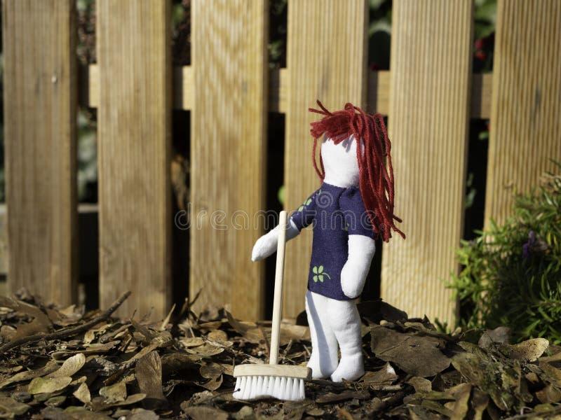 Petite poupée de chiffon tenant un balai dehors avec des feuilles de chute au sol photos libres de droits