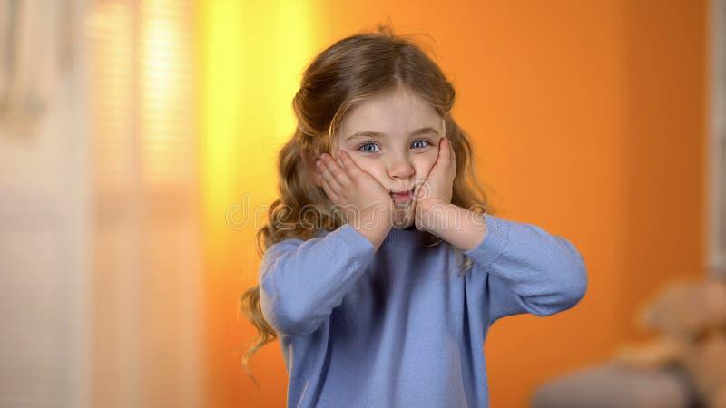 Petite princesse mignonne jouant et faisant le visage dr?le ? la cam?ra, enfant en bonne sant? photos libres de droits