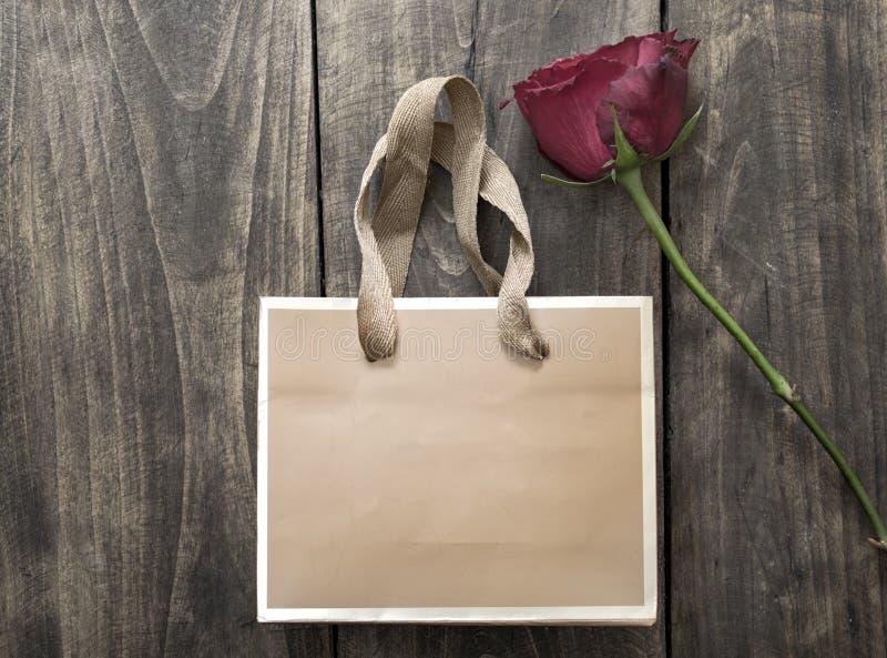 Petite rose de sac et de rouge sur le fond en bois image stock