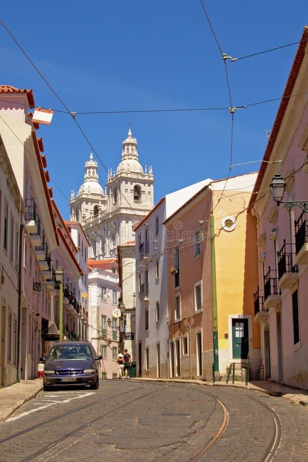Petite rue à Lisbonne avec des tours de la cathédrale dans le dos photographie stock libre de droits