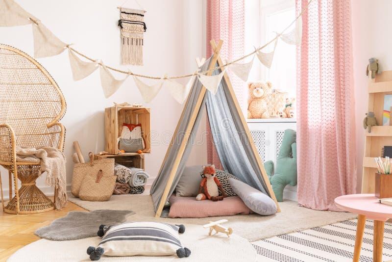 Petite salle de jeux rose mignonne de princesse dans la conception scandinave avec la chaise, les oreillers, les tapis, les jouet photos libres de droits