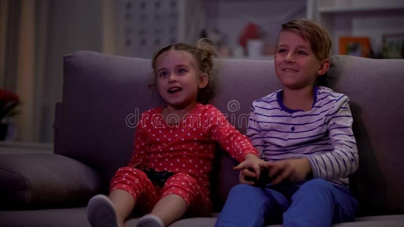 Petite soeur prenant à frères la manette, desserrant le jeu vidéo, ayant l'amusement ensemble image libre de droits