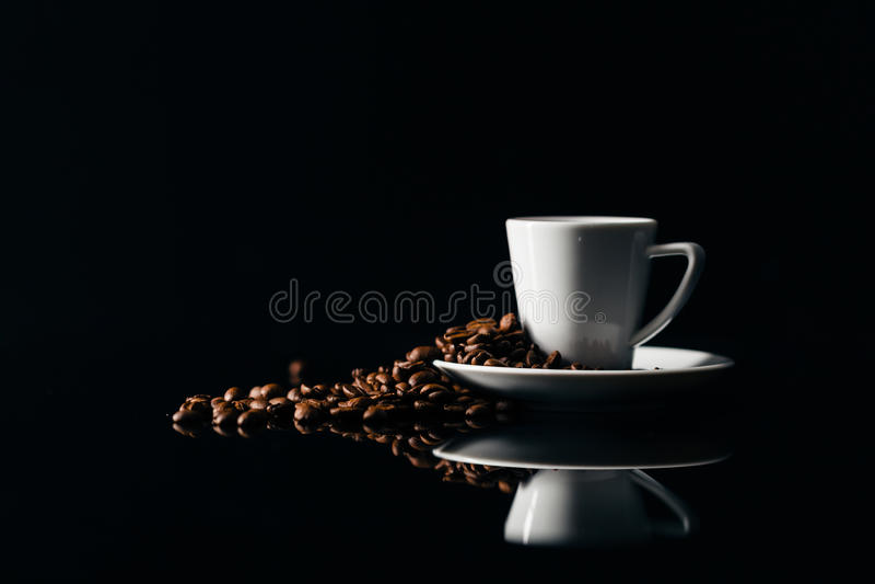 Petite tasse de café noir sur un fond foncé avec des grains de café photographie stock