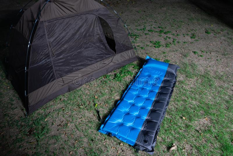 Petite tente campante et un lit d'air bleu sur un champ d'herbe au terrain de camping d'heures de nuit photo libre de droits