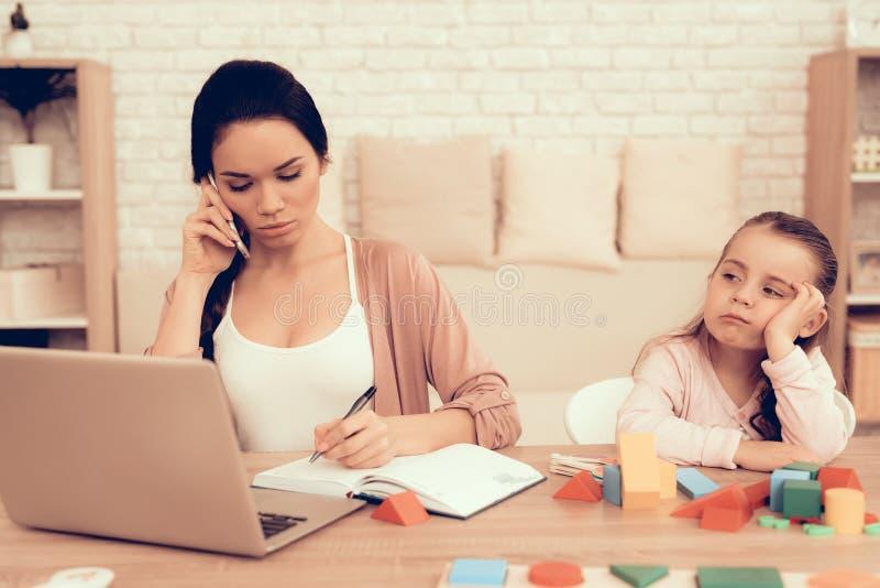 Petite travail triste de fille et de mère sur l'ordinateur portable à la maison photographie stock