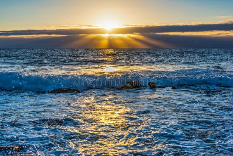Petite vague sous un soleil brillant au coucher du soleil photographie stock