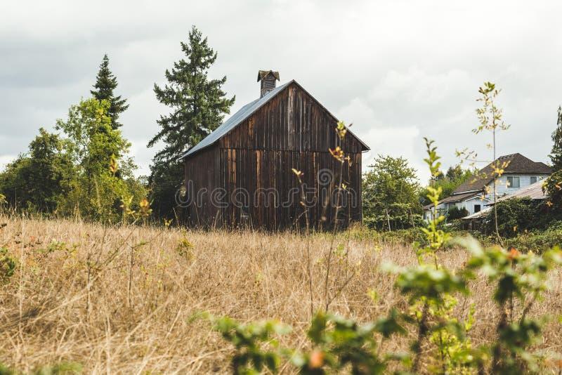 Petite, vieille, brune grange dans le voisinage rural image stock