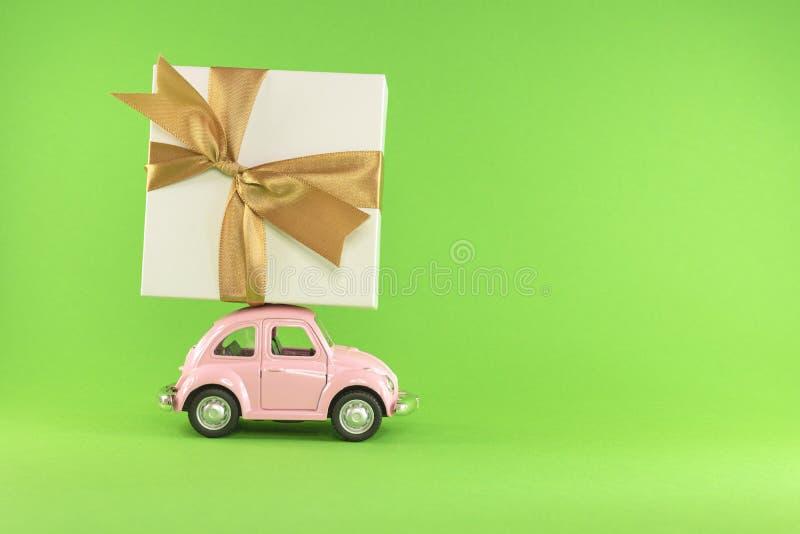 Petite voiture modèle jouet rétro avec boîte cadeau présente sur fond vert clair Noël, anniversaire, jour des valentines images libres de droits