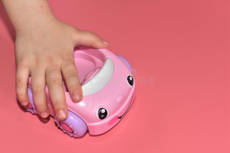 Petite voiture rose de jouet de plan rapproché dans la jolie main de l'enfant sur le fond rose Copyspace image stock