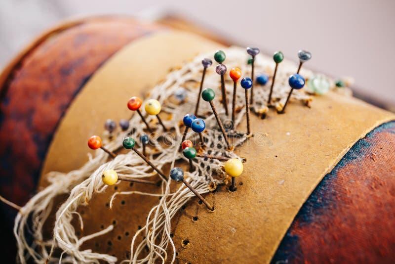 Petites aiguilles avec les astuces colorées dans un oreiller en cuir Concept de couture photographie stock libre de droits