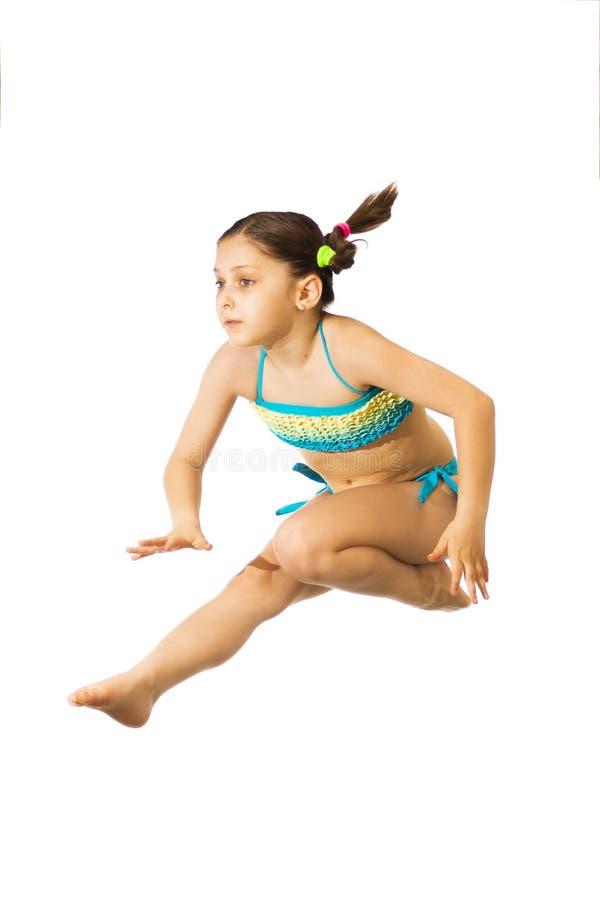 Petites 8 années femelles caucasiennes de fille dans le swimmwear multicolore sautant sur le fond blanc image stock