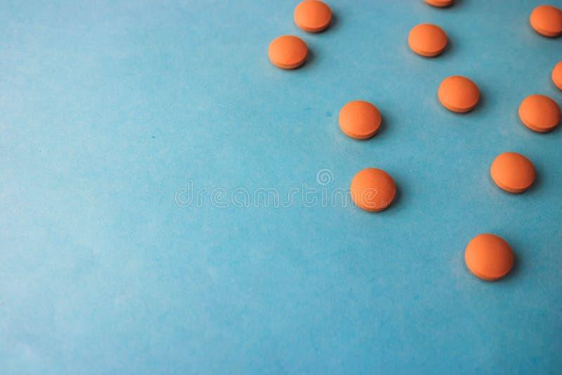 Petites belles pilules rondes pharmaceptic médicales jaune-orange, vitamines, drogues, antibiotiques sur un fond bleu, texture image stock