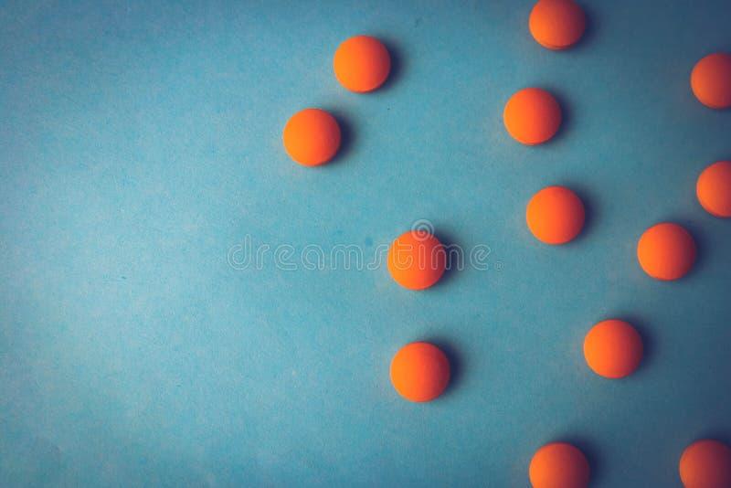 Petites belles pilules rondes pharmaceptic médicales jaune-orange, vitamines, drogues, antibiotiques sur un fond bleu, texture photographie stock