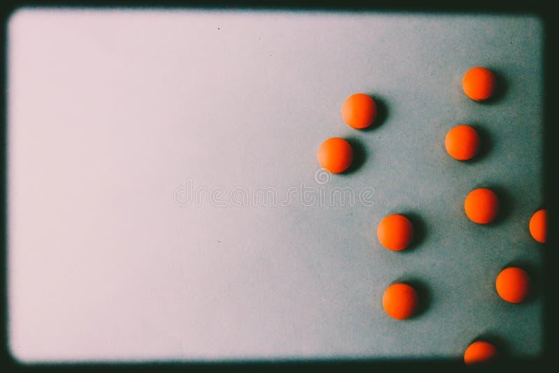 Petites belles pilules rondes pharmaceptic médicales jaune-orange, vitamines, drogues, antibiotiques sur un fond bleu, texture photographie stock libre de droits