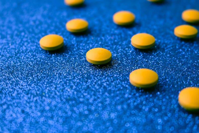 Petites belles pilules rondes pharmaceptic médicales jaune-orange, vitamines, drogues, antibiotiques sur un fond bleu, texture photos libres de droits