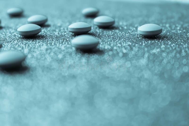 Petites belles pilules rondes pharmaceptic médicales jaune-orange, vitamines, drogues, antibiotiques sur un fond bleu, texture photo stock