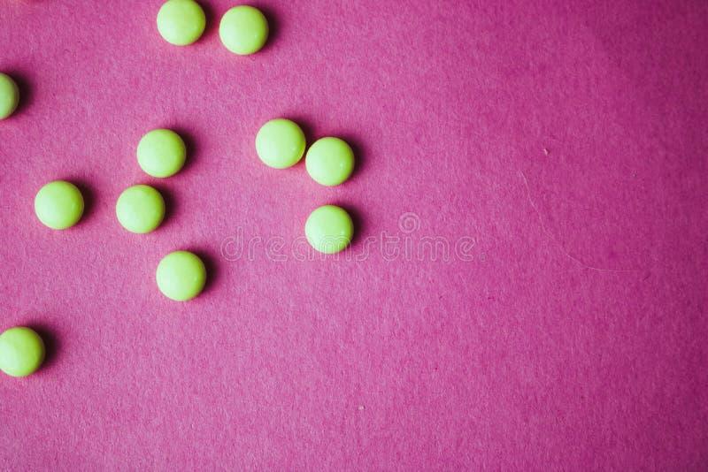 Petites belles pilules rondes pharmaceptic médicales jaune-orange, vitamines, drogues, antibiotiques sur un fond pourpre rose, te photos libres de droits