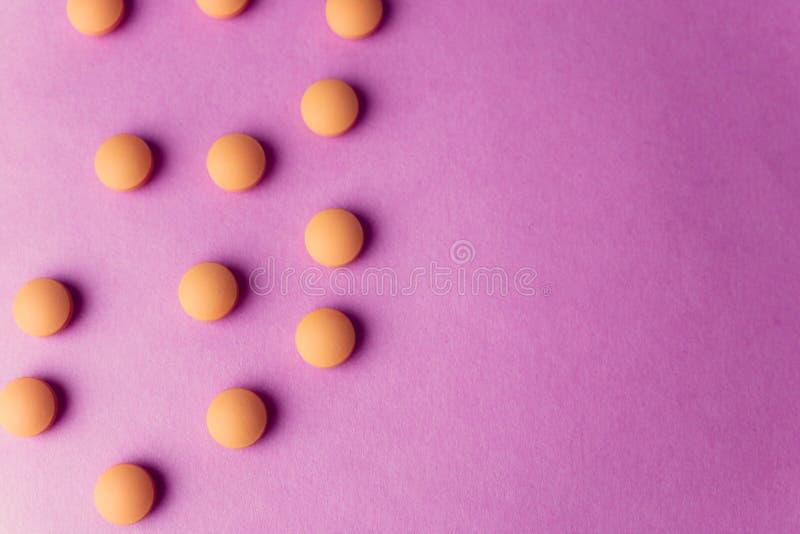 Petites belles pilules rondes pharmaceptic médicales jaune-orange, vitamines, drogues, antibiotiques sur un fond pourpre rose, te photographie stock libre de droits