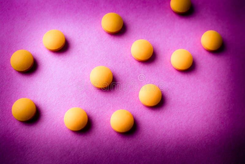 Petites belles pilules rondes pharmaceptic médicales jaune-orange, vitamines, drogues, antibiotiques sur un fond pourpre rose, te images libres de droits