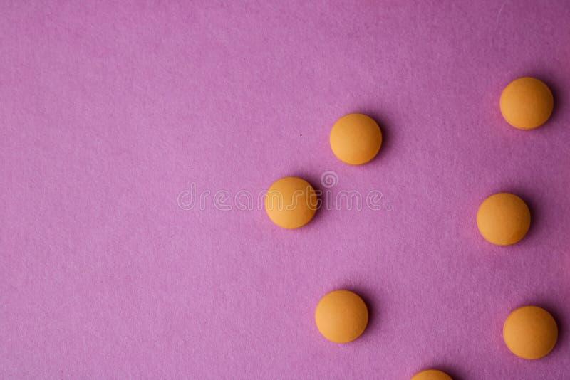 Petites belles pilules rondes pharmaceptic médicales jaune-orange, vitamines, drogues, antibiotiques sur un fond pourpre rose, te images stock