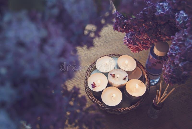 Petites bougies blanches dans un panier, une huile de massage et une essence photo stock