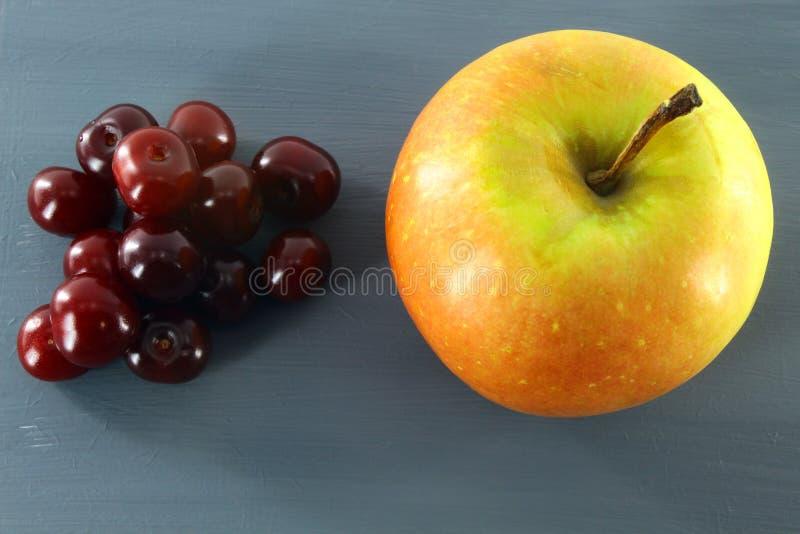 Petites cerises mûres et un Apple frais sur un fond gris photos stock