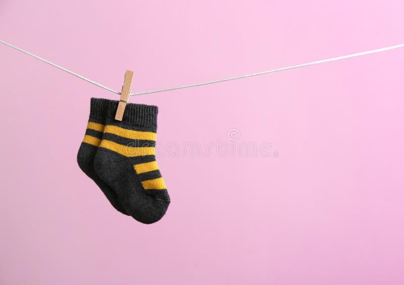 Petites chaussettes accrochant sur la ligne de lavage sur le fond de couleur Accessoires de b?b? photographie stock