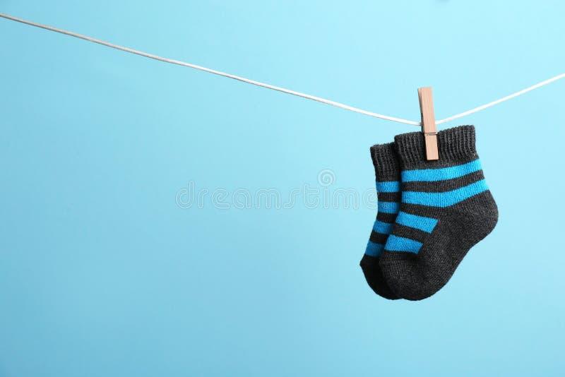 Petites chaussettes accrochant sur la ligne de lavage sur le fond de couleur, l'espace pour le texte image stock