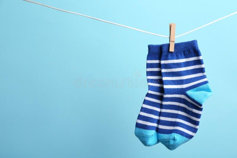 Petites chaussettes accrochant sur la ligne de lavage sur le fond de couleur, l'espace pour le texte photos libres de droits