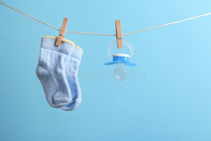 Petites chaussettes et t?tine accrochant sur la ligne de lavage sur le fond de couleur, l'espace pour le texte image libre de droits