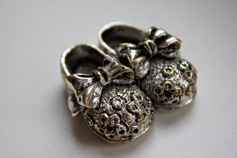 Petites chaussures argentées avec des arcs sur le fond blanc Cadeau, souvenir et bijoux photo stock