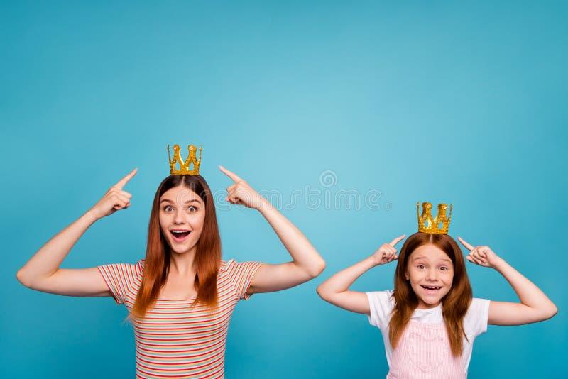 Petites dame excitée et maman rusées indiquant le headwear de doigts habillé à l'arrière-plan bleu d'isolement par équipement occ image stock