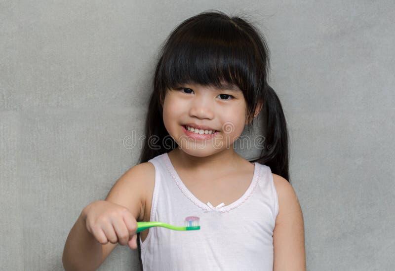 Petites dents mignonnes asiatiques de brosse de fille photographie stock libre de droits