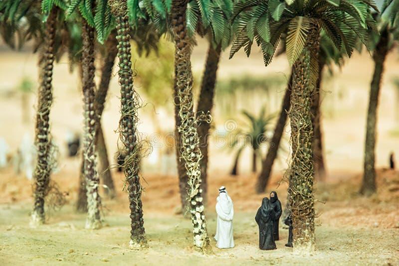 Petites figurines des Arabes dans l'oasis de désert sous le tre de paume photographie stock