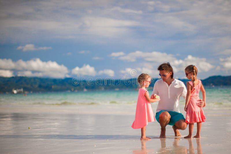 Petites filles adorables et jeune père sur tropical photographie stock