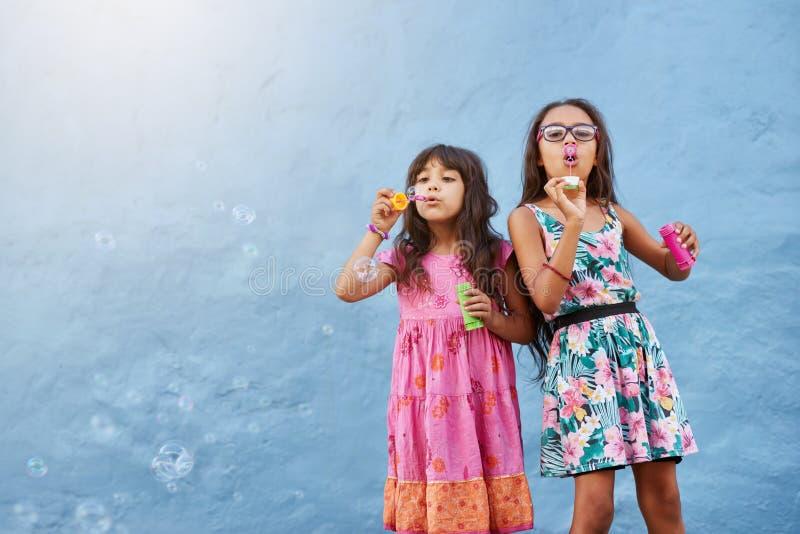 Petites filles adorables soufflant des bulles de savon photos stock