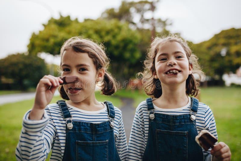 Petites filles avec une bouche sale tout en mangeant la crème glacée  image libre de droits