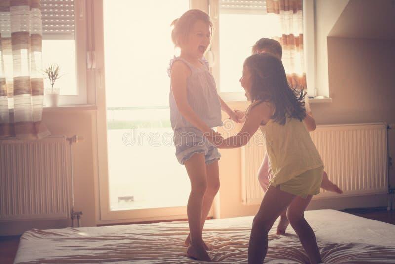 Petites filles ayant l'amusement ensemble dans le lit photographie stock libre de droits