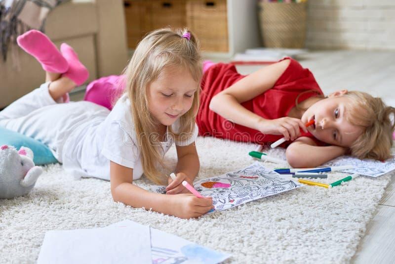 Petites filles colorant sur le plancher photos libres de droits
