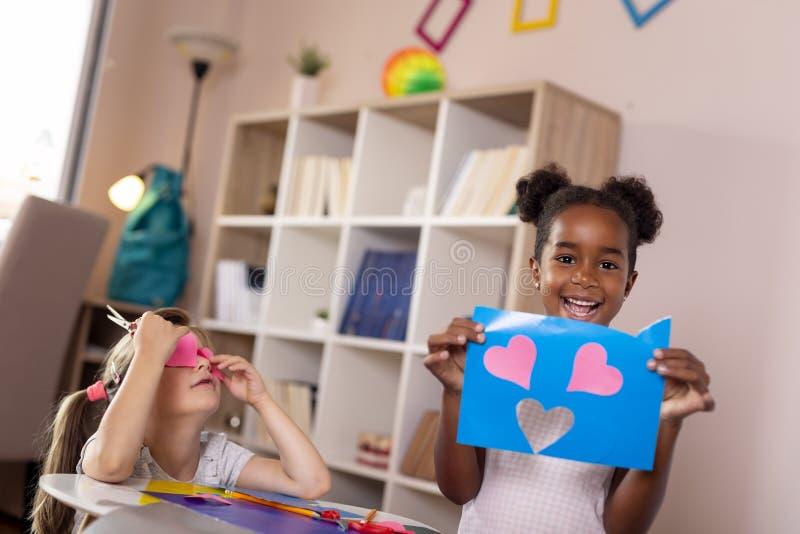 Petites filles coupant les papiers colorés photographie stock
