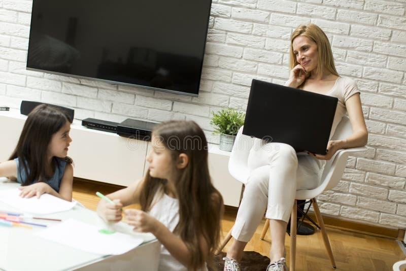 Petites filles dessinées dans la chambre tandis que maman parlant au téléphone images libres de droits