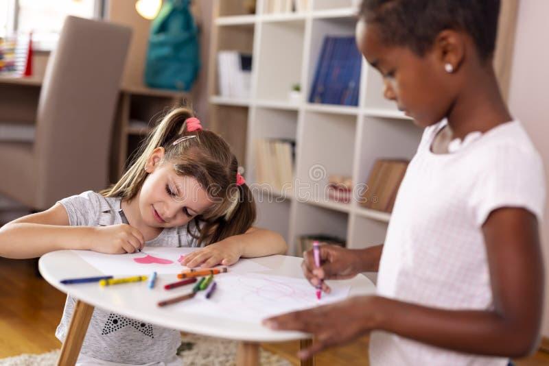 Petites filles dessinant avec des crayons images stock