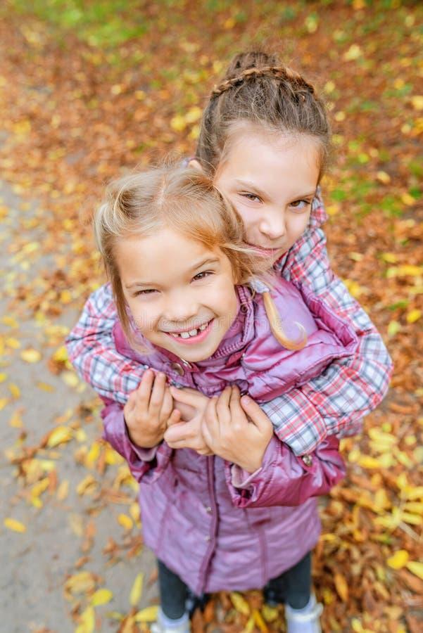 Petites filles enterrées dans le jaune de feuilles d'automne image stock