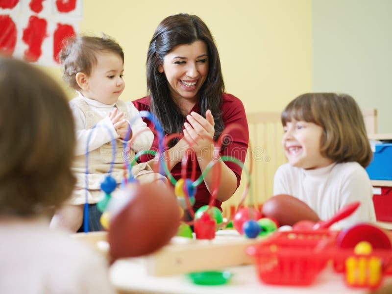 Petites filles et professeur féminin dans le jardin d'enfants photos stock