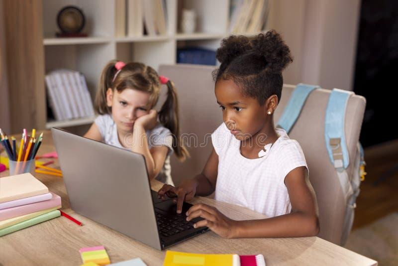 Petites filles faisant le travail sur un ordinateur portable photographie stock