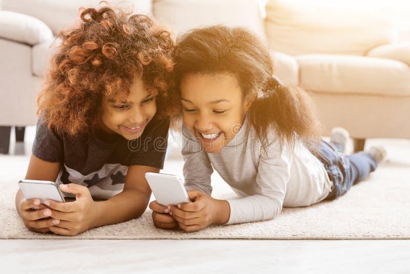Petites filles heureuses avec des smartphones se trouvant sur le plancher image libre de droits