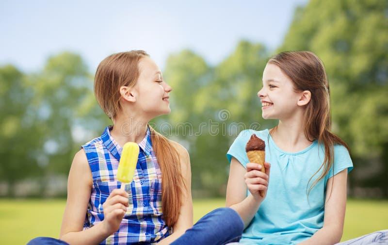 Petites filles heureuses mangeant de la glace en parc d'été image libre de droits
