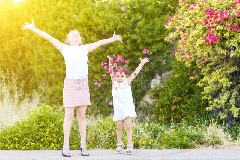 Petites filles jetant les pétales roses au-dessus photos stock